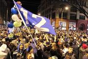 """With a """"12"""" flag flying, a big crowd of Seahawks fans floods First Avenue in Pioneer Square after the Seahawks win the Super Bowl."""