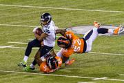 Seattle receiver Golden Tate gets brought down after a catch by Brandon Marshall and Nat Irving.