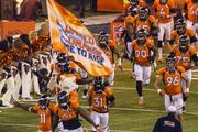 The Broncos rush onto the field before the game.
