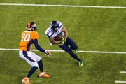 Seattle receiver Percy Harvin makes a big gain on a reverse as Denver defender Mike Adams closes in.