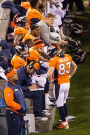 Peyton Manning and Wes Welker talk on the bench late during a blowout loss.