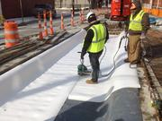Workers installed a dielectric membrane at the intersection of Elm and Findlay streets, where a high-voltage electric line crosses under the track slab, for extra insulation.