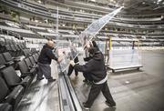 The glass boards around the hockey rink get installed to keep errant pucks from shooting into the crowd.