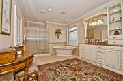 The master bathroom has custom leaded glass windows and a doubled ended tub.
