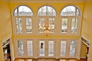The grand foyer has two-story leaded glass windows.