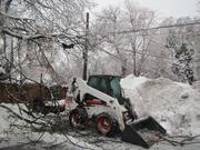 A skid-steer loader in Bala Cynwyd, Pa., is surrounded by a snow pile and downed tree limbs.
