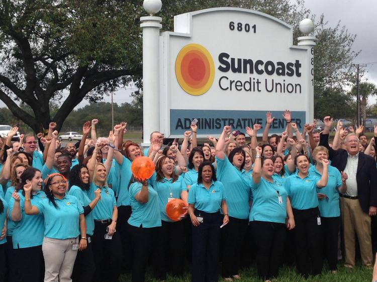 Employees of Suncoast Credit Union cheer as the company unveils its new sign after converting from a federal charter to a state charter.
