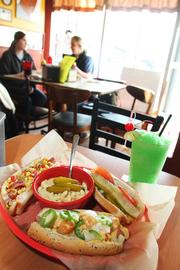 Dirty Frank's has several different hot dog varieties, including the Ohioana, Sarva's Tot-cho and the Chicago Dog, pictured with a side of macaroni and cheese and a Limeaid slushie.