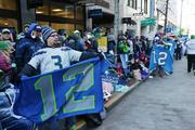 "Before the parade's start, fans with ""12"" signs for the ""12th Man"" crowd the sidewalks near the start of the parade route on Fourth Avenue in Seattle. Traffic was jammed and buses and trains were packed as Seattle fans braved the cold Wednesday morning to get to the parade."