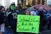 "One girl's sign reads: ""Schools cool but the Seahawks RULE"" in the crowd awaiting the start of the Seattle Seahawks parade in Seattle on Wednesday.  Students initially were told they would have to take unexcused absences Wednesday, but officials later relented on that policy."
