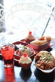 """Surly Girl favorites include the Surly Temple, a homemade red velvet cupcake and veggie Frito pie. Pictured in the rear is a """"super supper tray"""" with chicken pot pie, steamed broccoli, poblano mashed potatoes and an orange and raspberry butter-cream cupcake."""