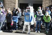 "A fan dressed as a robot ""12th Man"" joins the crowd on the sidewalk near the start of the Seahawks championship parade in Seattle on Wednesday morning."
