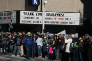 "A giant sign at the Cinerama theater in downtown Seattle reads ""THANK YOU SEAHAWKS!"" as crowds of people await the championship parade Wednesday morning. The theater is owned by Seahawks owner Paul Allen."
