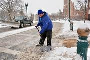 Joe Diamond, who works for the Downtown Schenectady Improvement Corp., cleans up after the storm.