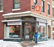 Sean Richards, an employee at Pizza King in Schenectady, NY, clears the sidewalk for customers.