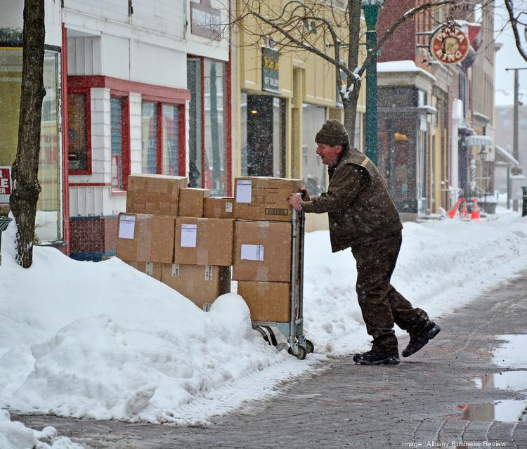 A driver for United Parcel Service wades through the snow while making a delivery on Jay Street in Schenectady, NY.