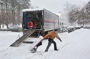Chuck Kubly, a Sysco employee, makes a delivery through the snow at Union College in Schenectady, NY.