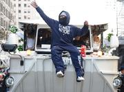 """In full """"Beast Mode"""" apparel, Seattle Seahawks running back Marshawn Lynch tosses Skittles to the crowd as he rides in the Seattle Seahawks Super Bowl XLVIII victory parade."""