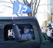 "Seattle Seahawks owner Paul Allen waves a ""12"" flag as he rides in the Seattle Seahawks championship parade through downtown Seattle on Wednesday."