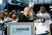 Head coach Pete Carroll, and Jeremy Lane (holding trophy) listen to the cheering fans at CenturyLink stadium to celebrate the Seahawks Super Bowl victory.