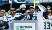Seahawks Marshawn Lynch (second from right) and quarterback Russell Wilson (right) cheer on the crowd at CenturyLink during the Super Bowl victory celebration.