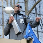 Seahawks player Doug Baldwin sports a home made Super Bowl trophy that a fan handed to him during the parade. Seattle police early on estimated that more than 700,000 people turned out of the Seahawks Super Bowl victory parade on 4th Avenue in downtown Seattle.