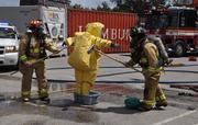Mission accomplished: A hazmat team member is scrubbed down.