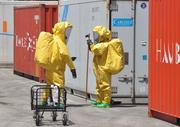 A hazardous materials team searches for the source of the contamination.