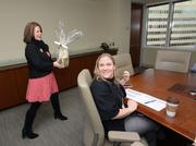 MSPBJ Publisher Tammy Mencel delivers the good news to 2014 40 Under 40 honoree Nicki Donlon of Baker Tilly (seated).