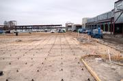 Parking lot infrastructure is in place at the foreground with rebar in place for a foundation pour.