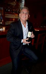 Reynolds Family Winery owner Steve Reynolds shows off a bottle of his wine at Nina's Ristorante. The mustard flower, which grows in abundance around the Napa Valley, is hand-pressed into select bottles of Reynolds Family wines.