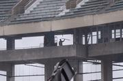 A worker clears debris from the upper level.