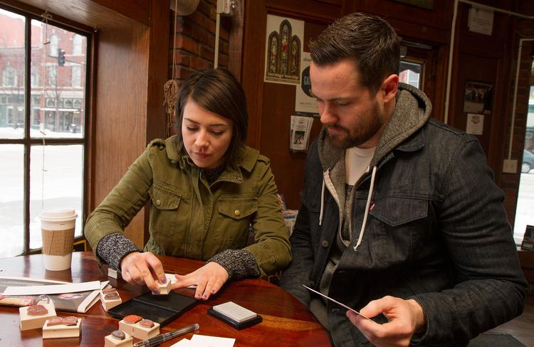 Hannah Scott and Kevin Wildt of Stamp Yo Face! test out newly made custom stamps Friday morning at Mead's Corner, 430 E Douglas Ave.