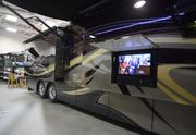A big-screen television dresses the outside of the Entegra Coach Aspire.