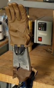 """A finished """"Convoy"""" glove for the military is placed over a heated hand mold as part of the final finishing of the glove to pre-curve the glove at Outdoor Research's production facility in Sodo."""