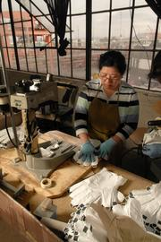 Que To bonds Gore-Tex linings to gloves for the military at Outdoor Research's production facility in Sodo.