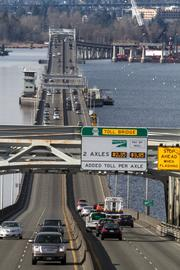 The toll sign and cameras on the I-520 Bridge heading west to Seattle over Lake Washington.