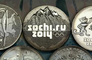 The Olympic rings sit on 25 ruble denomination coins, commemorating the upcoming Sochi 2014 Winter Olympics, in this arranged photograph at the OAO Sberbank headquarters in Moscow, Russia.