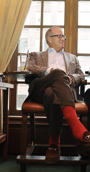 Sporting orange socks in support of the Denver Broncos, Kaufman chats with Bill Husted at the U-Club