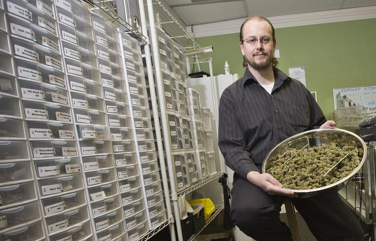 """Dave Hodges, the owner of A2C2, holds a pound of """"The Force,"""" and exclusive strain of cannabis that is grown for the All American Cannabis Club.  This room is called the peer counseling room. Members come here to decide which product is best for them, from flowers to edibles and concentrates."""