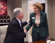 Sandy Shugart of Valencia College greets Ann McGee of Seminole State College as she arrives.