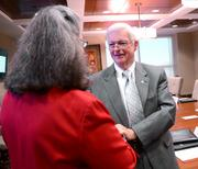 Dan Holsenbeck of the University of Central Florida greets Wendy Libby of Stetson University as she arrives at the Burr & Forman offices.
