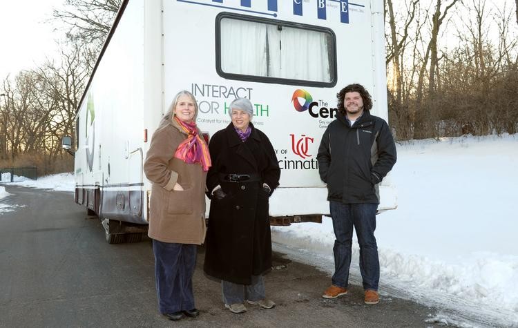 Ann Barnum, senior program officer at Interact for Health (left), Dr. Judith Feinberg, professor of internal medicine at the University of Cincinnati, and Adam Reilly, project director for the Cincinnati Exchange Project, stand by the RV being used for the Cincinnati Exchange Project.