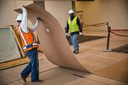A worker removes covering that protected the wooden floors in RDU's Terminal 1 in preparation of the March 2 grand opening.