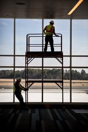 Workers clean the windows at the newly renovated Terminal 1 building at RDU.