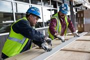 Workers measure and cut wooden paneling that will be used in the renovation of RDU's Terminal 1.