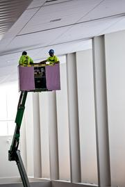 Workers check ceiling panels at RDU's Terminal 1.