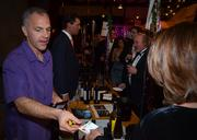 Eric Reichenbach, assistant winemaker to Robert Foley at Robert Foley Vineyards, hands a business card to an attendee interested in the winery.