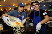 Darin Goo, left, Department of Transportation engineer, and Mike Watanabe, creative director of Brain Pop-Interactive Programs, cooking up vegetables at the Punahou Carnival.  Goo and Watanabe are 1991 alumni of the private school.
