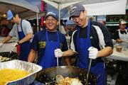Jose Elizaga, left, sales associate at Galderma Laboratory and Darryl Nakamoto, CEO of Kaiuli Energy, frying up vegetables at the Punahou Carnival.
